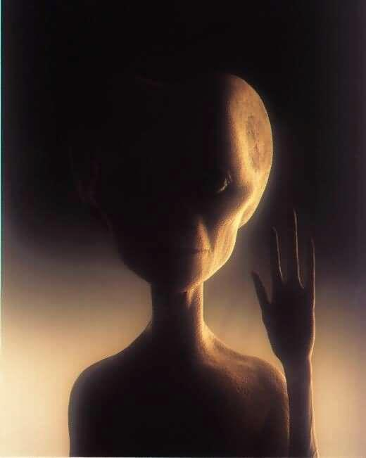 Grey Alien being holding his hand up with peace