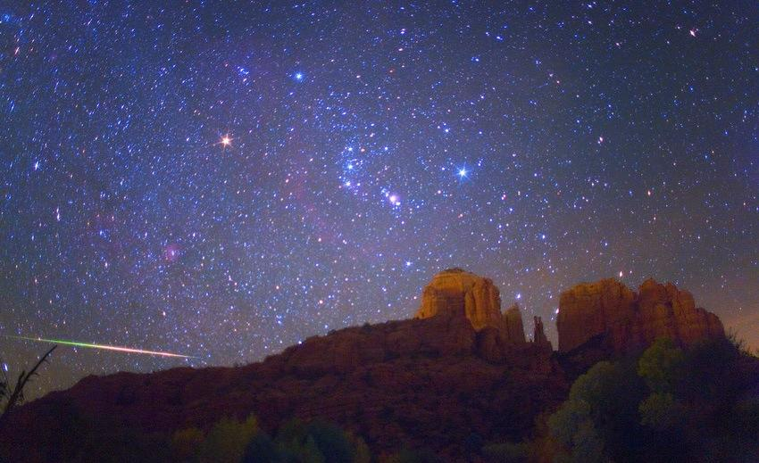 Glowing night sky of stars above Sedona's Cathedral Rock